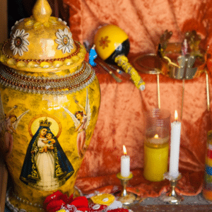 Yellow Urn with La Virgen de Guadalupe on an altar surrounded by Candles.